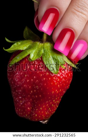 Fingers with beautiful manicure hold juicy strawberries. - stock photo