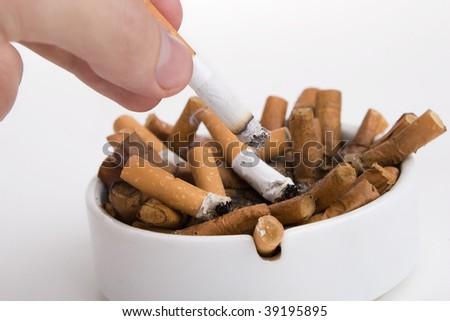 Fingers with cigarette butt in an ashtray
