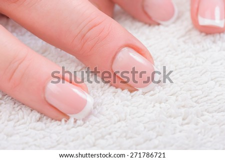 Fingers with french manicure on white towel - stock photo