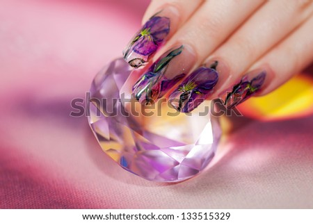 Fingers with long acrylic fingernails and beautiful manicure touch a shining diamond - stock photo