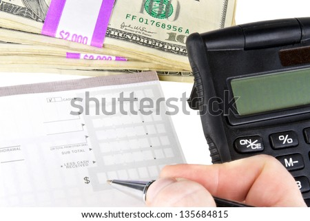 fingertips of a hand holding an ink pen while completing a blank bank deposit slip. A black calculator and a stack of 100 dollar USA currency bills wrapped in 2000 dollar bundles.  - stock photo