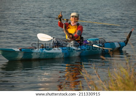 finish fishing on the kayak at reservoir by fisherman - stock photo