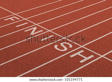 Finish Line as a business symbol of success in completing a planned strategy to achieve victory and reach the goals of financial freedom and wealth as a track and field background in perspective. - stock photo