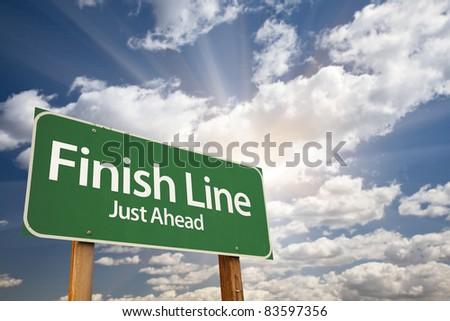 Finish Line, Just Ahead Green Road Sign Over Dramatic Sky, Clouds and Sunburst. - stock photo