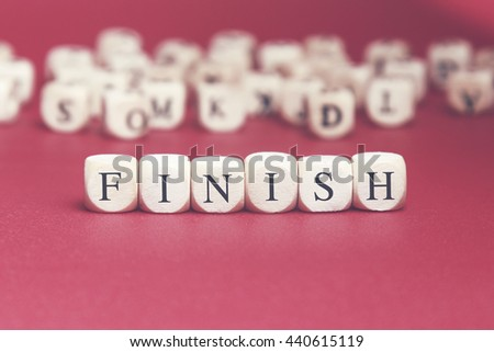 Finish word written on wood cube with red background