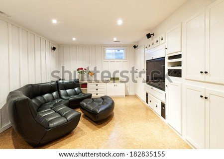 Finished basement of residential home with entertainment center, couch and flat screen television. - stock photo