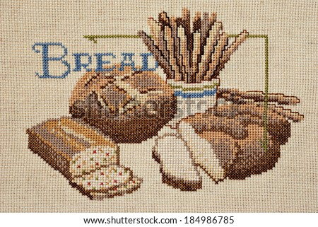Finished cross stitch design of bread still life (worked on homespun aida cloth)  - stock photo