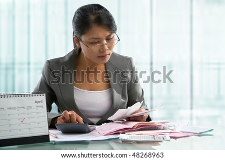 Finishing calculation for tax form on April 15 concept, with calendar in front - stock photo