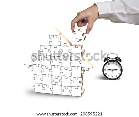 Finishing to assemble house shape puzzles with alarm clock isolated on white - stock photo