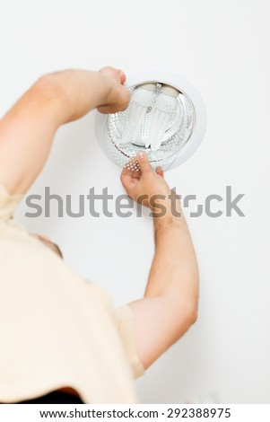 Finishing touches in mounting light by an electrician. - stock photo