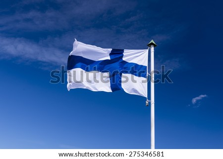 Finnish national flag waving on wind against blue cloudy sky