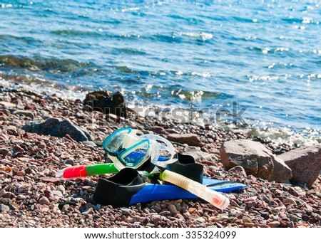 fins, mask and snorkel lying on the beach near the edge in anticipation of a swimmer - stock photo