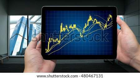 Fintech concept .Man hand holding tablet with stock market chart graph .Window showing smart building background