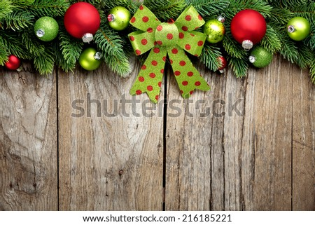 Fir branch and Christmas balls on wooden background - stock photo