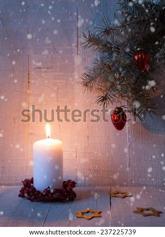 Fir branch, candle and  Christmas decorations on the old  wooden plank.  - stock photo