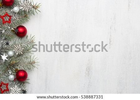 Fir branch with Christmas decorations on old wooden shabby background with copy space for text.