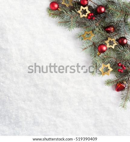 Fir branch with Christmas decorations on the background of natural snow.
