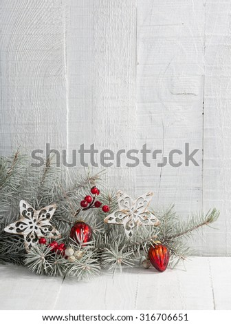 Fir branch with Christmas decorations on the white wooden plank.  - stock photo