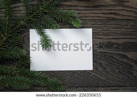 fir branch with paper card on oak table from above, christmas background - stock photo