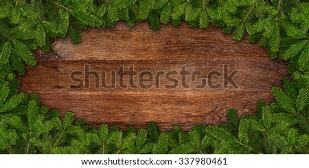 fir branches frame on wooden background - stock photo