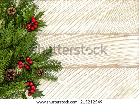 Fir tree and holly branches decoration for Christmas on wooden background - stock photo