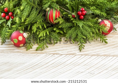Fir tree and holly branches decoration with red Christmas balls on wooden background - stock photo