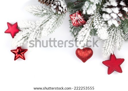 Fir tree branch with christmas decor covered with snow. Isolated on white background - stock photo