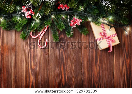Fir tree branch with christmas lights, gift box and candy canes on wooden background with copy space - stock photo