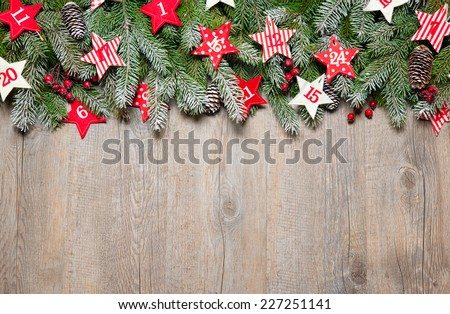 Fir tree  branches and advent calendar stars on old wooden board - stock photo