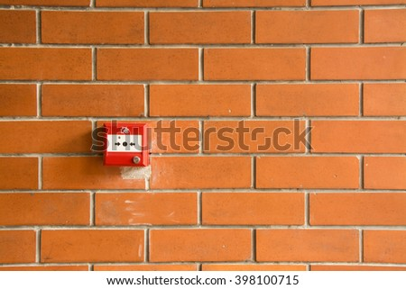 Fire alarm on the orange brick wall. - stock photo