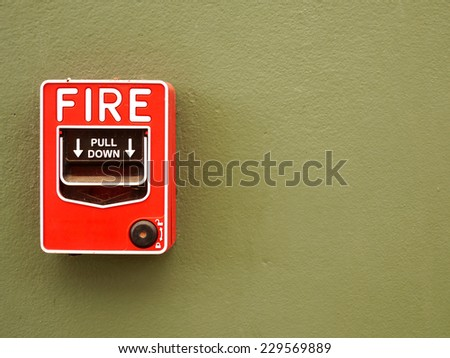 Fire alarm switch on green wall background.