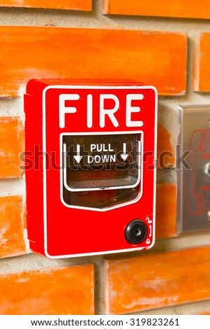 Fire Alarm Switch on the orange brick wall background texture. - stock photo