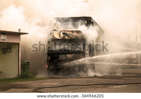 Fire and black smoke on the road after a truck collision - stock photo