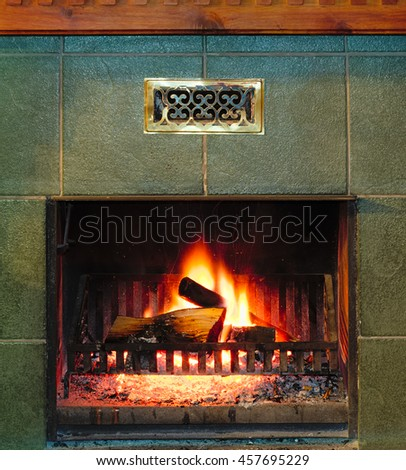Fire and burning firewood in old fireplace with green old-fashion tiles - stock photo