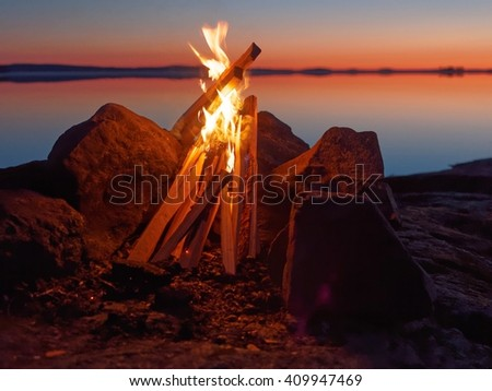 Fire and flames of atmospheric campfire on the beach at night. Still water of the lake on the backgound with warm colors of sunset. Very shallow dept of field.      - stock photo