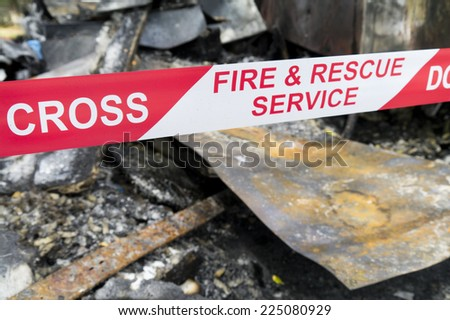Fire and Rescue Do Not Cross tape around burnt fire scene. - stock photo