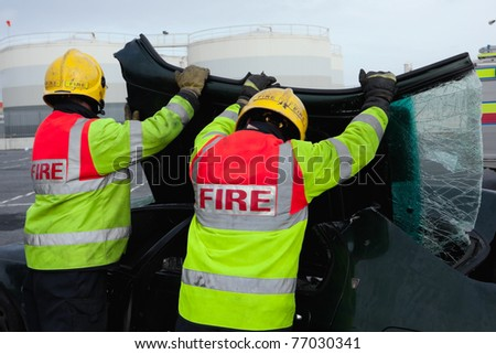 Fire and Rescue emergency Units at car accident removing broken wind screen - stock photo
