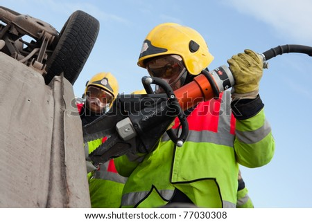 Fire and Rescue emergency Units in action with Power Wedge at car accident - stock photo