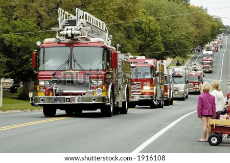 Fire and rescue vehicles being driven in a fire muster parade.