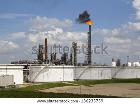 Fire and smoke from an oil refinery pipe with silos in Rotterdam industrial area in Holland - stock photo