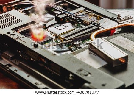 Fire and smoke on chip on damaged computer or laptop  - stock photo