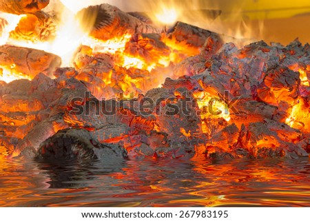 fire ashes and embers of a campfire - stock photo