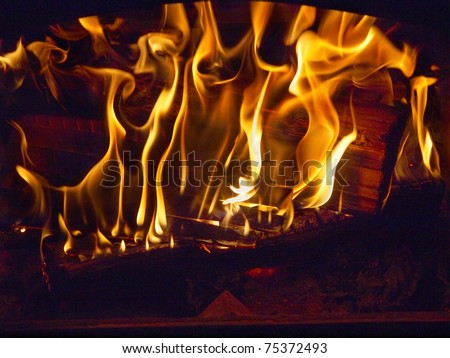Fire blazing in the fireplace with decorative screen - stock photo