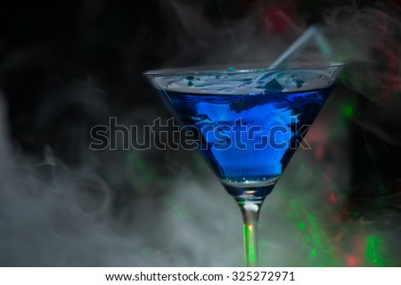 Fire blowing out of blue lagoon glass/close-up with black background and laser effects - stock photo