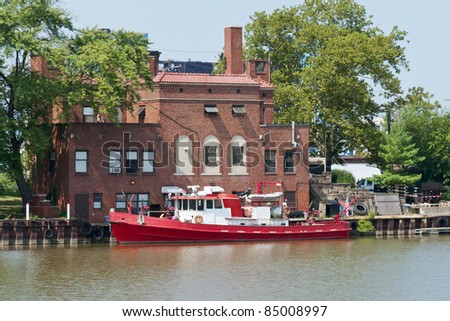 Fire Boat on the River A boat equipped for fire fighting is docked at a brick fire station on the Cuyahoga River in Cleveland, Ohio - stock photo