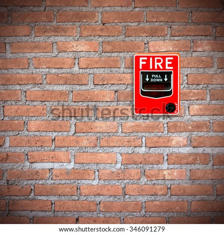 fire break glass alarm switch on the stone wall - stock photo