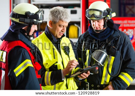 Fire brigade - Squad leader gives instructions, he used the Tablet Computer to plan the deployment - stock photo