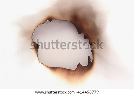 fire burned holes in paper (close up)
