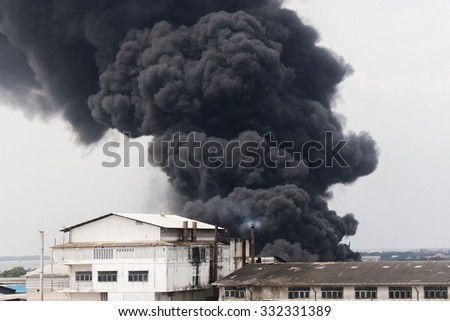 Fire burning and black smoke over the Factory. - stock photo