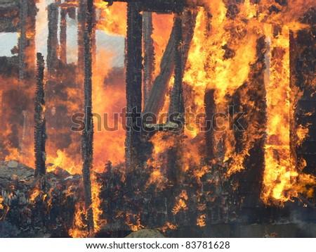 fire burning wooden frame house - stock photo